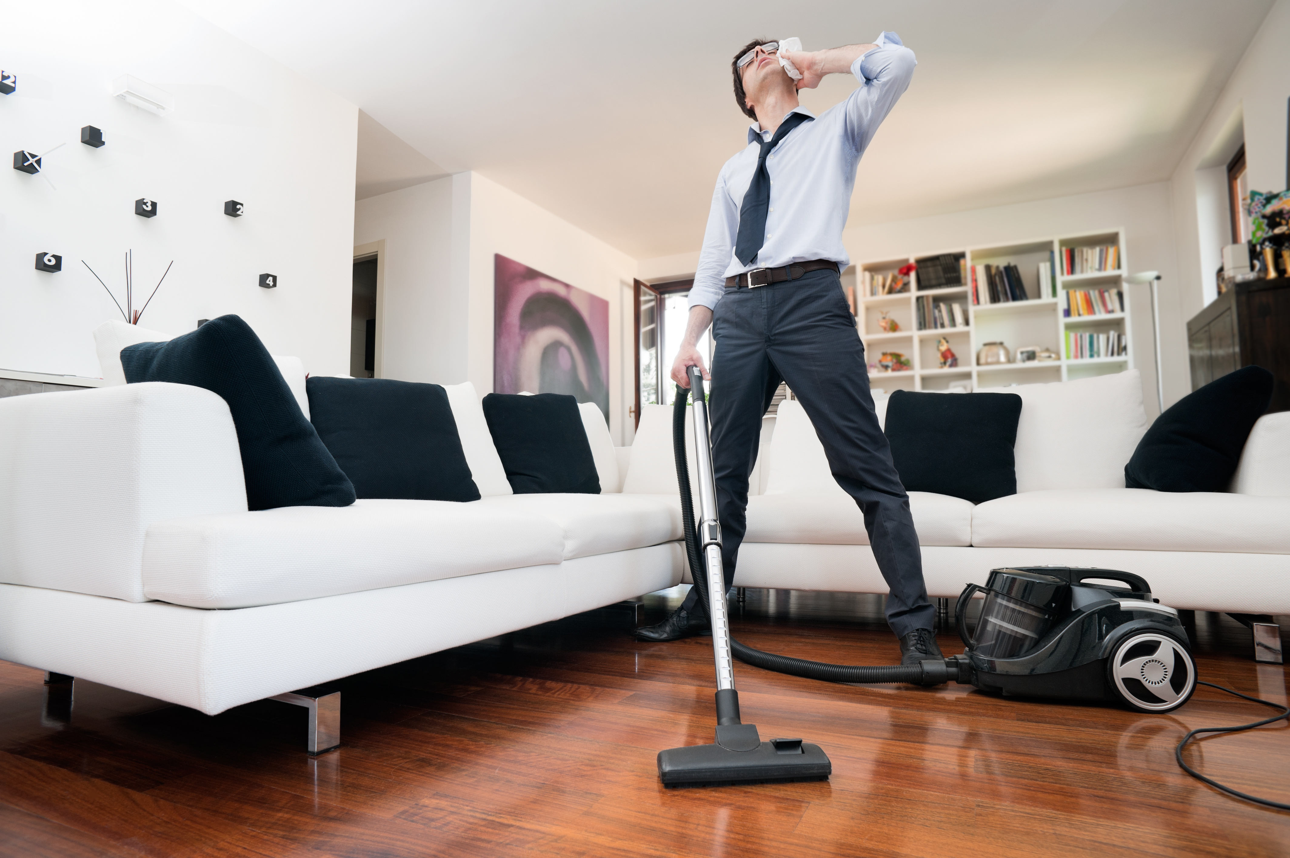 man sweating cleans the floor of the house